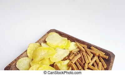 Slow movement of a dark wooden plate with chips and salted crackers, beer appetizer, junk food, close-up