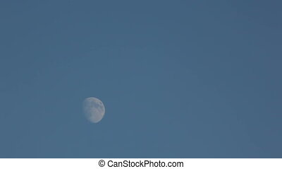 Slow movement of the Moon on the blue sky