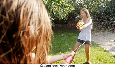 Slow mtoion footag eof two teenage girls playing with water...