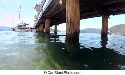 Slow mtoion footage of calm sea and old wooden pier on...