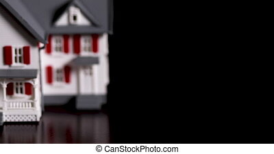 Slow Panning of Miniature Model House on Dark Wood Surface...