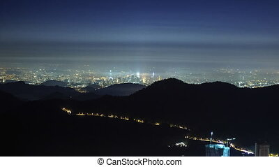 Slow rolling cloud over mountain valley with city lights in the background. Time lapse Zoom Out