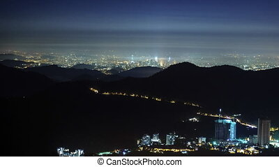 Slow rolling cloud over mountain valley with Kuala Lumpur city lights in the background. Time lapse