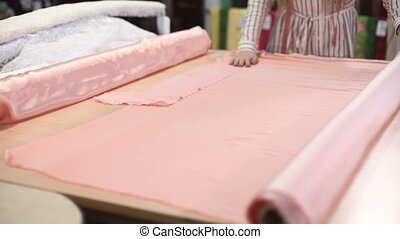 Slow shooting fabric store worker unwraps pink roll atlas...