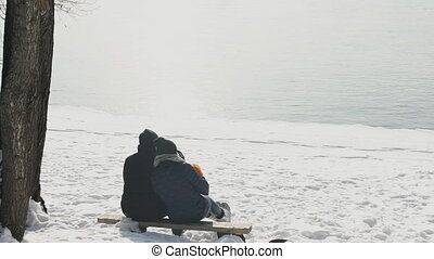 Slow shooting from back couple in winter on bank of lake outdoors