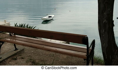 Slow shooting of river bank, bench and boat outdoors.