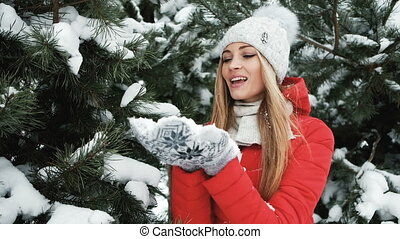 Slow shooting of woman blowing snow in frosty winter