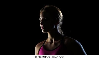 Slow shooting with the top down wonderful fitness lady on a black background. Slow motion. Close up