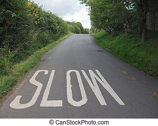 Slow sign painted on tarmac on a british road near a school