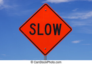 Slow Sign - orange slow road sign with black letters in...