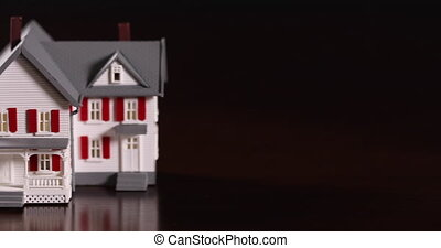 Slow Tracking Shot of Piggy Bank and Miniature House on Dark...
