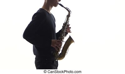Slow tunes on saxophone in the performance of young musician