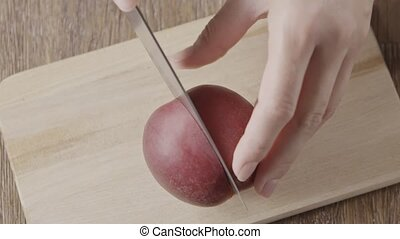 Slow motion video womans hands are cutting fresh natural organic ripe nectarine on two halves on a wooden board. Slow motion, 2K video, 240fps, 1080p.
