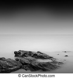 Daytime long exposure seascape with object in the sea. The photo taken in black and white. Black sea, Odessa, Ukraine