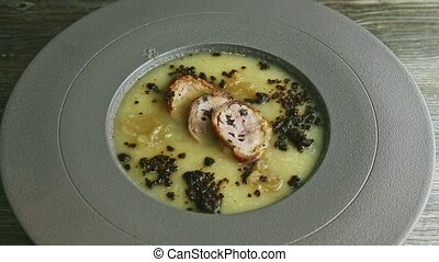 slow zoom in at exquisite decorated tasty onion cream soup with three pieces of homemade sausage served in modern gray deep plate on wooden table