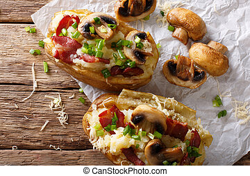 Slowly baked potatoes with bacon, mushrooms and cheese close-up. Horizontal top view