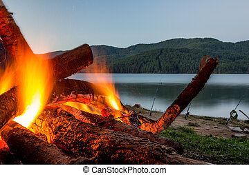 Slowly burning fire at lake shore