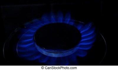 Slowly lights up the gas burner. Close up. Slow motion