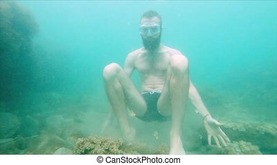 Slowly moving a young bearded man tries to meditate in a lotus pose at the bottom of the sea in the water. The concept of zen meditation and underwater yoga