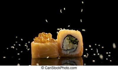 Slowmo sushi roll with salmon and caviar on black background rotating.