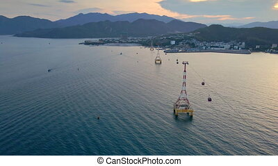 Slowmotion aerial shot of a cable car over a sea. Beautiful sunset shot of the city of Nha Trang, Vietnam.