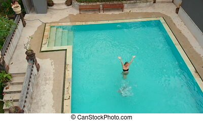 Slowmotion aerial shot of a young woman and her little son tourists having a good time in a swimming pool in a tropical surrounding. Tropical life concept.