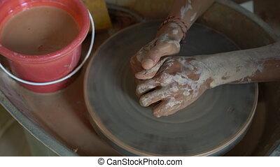 Slowmotion closeup shot of a teacher potter teaching his...