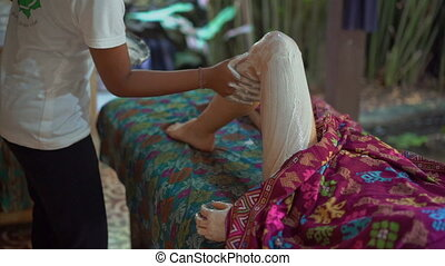 Slowmotion Closeup shot of a young woman in a tropical spa. beautician applies skin moisturizer compound on her skin.