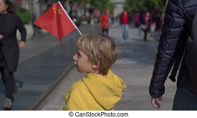 Slowmotion of a little boy holding a small Chinese flag walk...