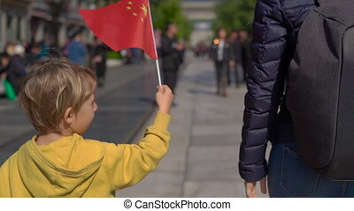 Slowmotion of a little boy holding a small Chinese flag walk the Quinmen Main Street Mall. The Forbidden City in the center of Beijing. the Walking street in a center of China's capital