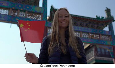 Slowmotion of a young woman bloger holding a small Chinese...