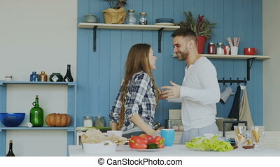 Slowmotion of Cheerful and attractive young couple in love dancing together rocknroll dance in the kitchen at home on holidays
