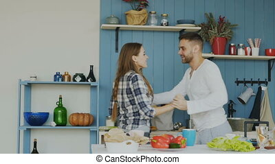 Slowmotion of Cheerful and attractive young couple in love dancing together latin dance in the kitchen at home on holidays