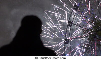 Slowmotion of closeup silhouette of alone man watching fireworks on new year celebration outdoors