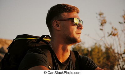 Slowmotion of Handsome young fashion man wearing sunglasses and backpack looks sunset in the field. 1920x1080 closeup