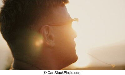 Slowmotion of Handsome young fashion man wearing sunglasses and backpack looks sunset in the field. In the mouth of a blade of grass. 1920x1080 closeup