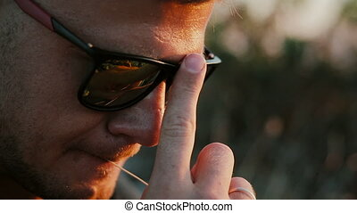 Slowmotion of Handsome young fashion man wearing sunglasses and looks sunset in the field. 1920x1080 closeup