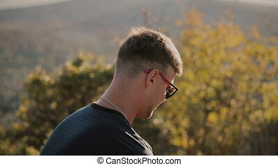Slowmotion of Handsome young fashion man wearing sunglasses and looks sunset in the field.