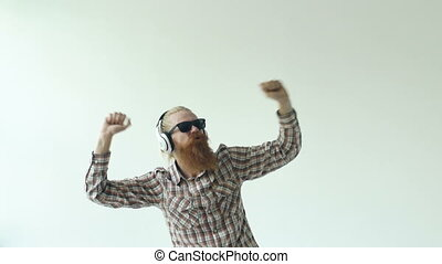 Slowmotion of Happy young bearded man in sunglasses and headphones dancing and listen music on white background