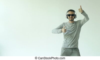 Slowmotion of Happy young man in sunglasses and headphones dancing and listen music on white background