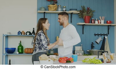 Slowmotion of joyful young couple have fun dancing while cooking in the kitchen at home