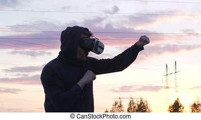 Slowmotion of silhouette of young man boxer in VR 360 headset training for kicking in virtual reality combat on sunset at city park