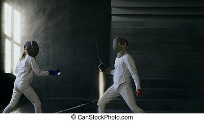 Slowmotion of Two fencers man and woman have fencing...