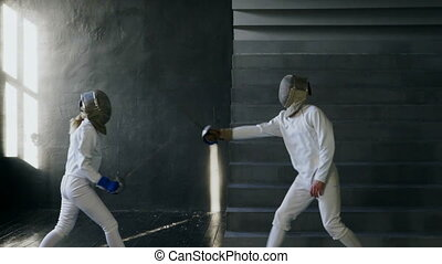 Slowmotion of Two fencers man and woman have fencing match...