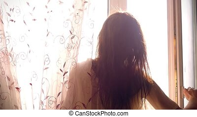 Slowmotion of young attractive sexy woman with slender body is opening curtain and looking out the window at the sunrise on a sunny morning