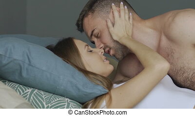 Slowmotion of young beautiful and loving couple kissing on bed in the morning