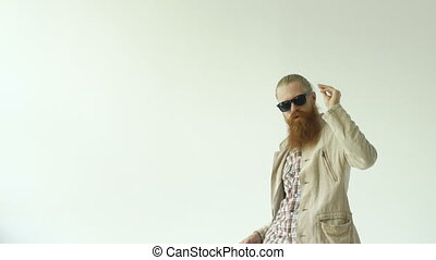 Slowmotion of young funny bearded man in sunglasses dancing on white background