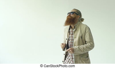 Slowmotion of young funny bearded man in sunglasses dancing...