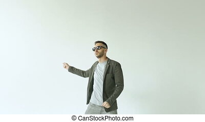 Slowmotion of Young funny man in sunglasses crazy dancing on white background