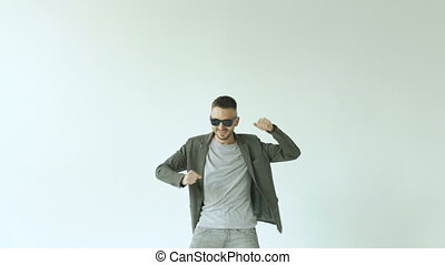 Slowmotion of Young funny man in sunglasses crazy dancing on...
